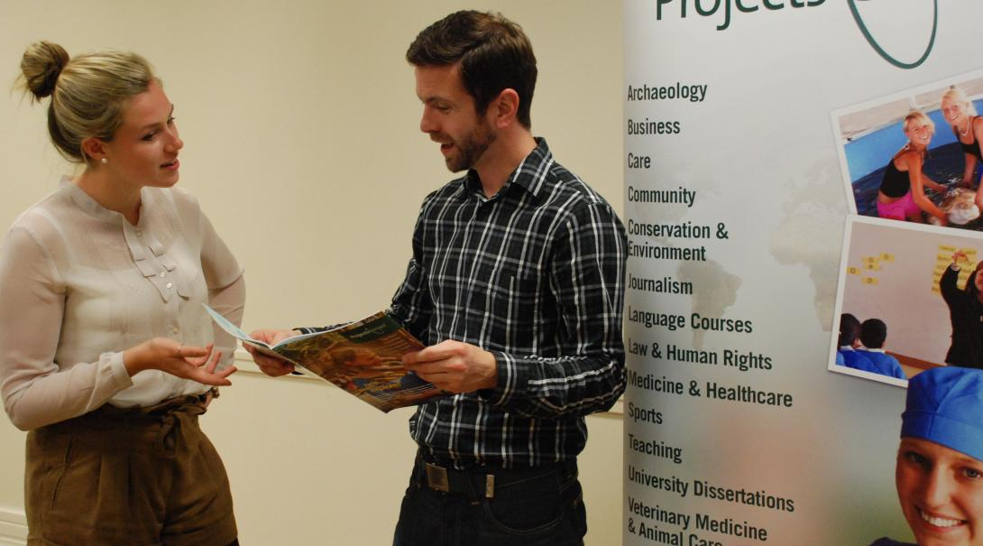 A prospective volunteer talks to a Projects Abroad staff member at an event in London.